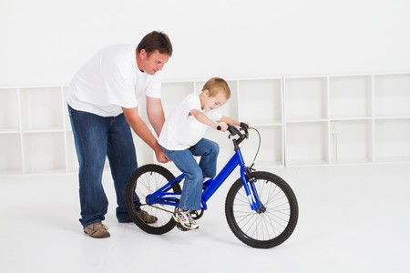 balancing: father teaching young son to ride bike Stock Photo