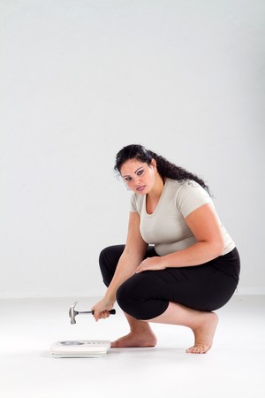 plus size woman: overweight woman hitting scale with hammer