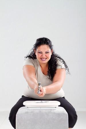 angry overweight woman smashing bathroom scale photo