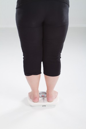 overweight woman standing on scale photo