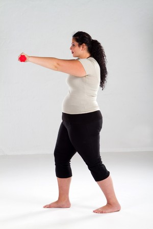 plus size woman: overweight woman lifting weights