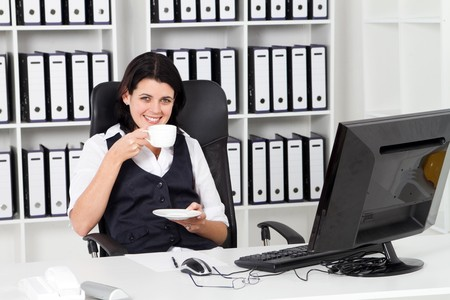 businesswoman drinking coffee in office photo