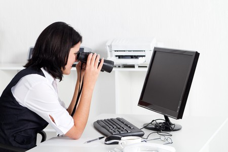 woman looking at computer through binoculars photo