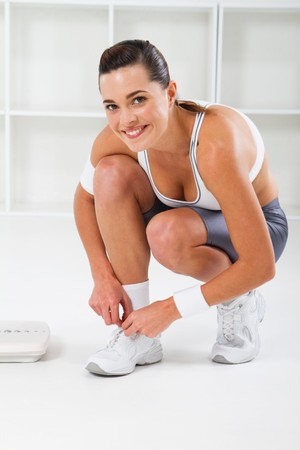 pretty fitness woman tying her shoes Stock Photo - 7639056