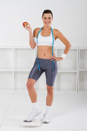 pretty fitness woman holding apple and tape measure Stock Photo - 7639000