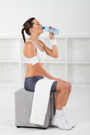 out of water: fitness woman drinking water after workout Stock Photo