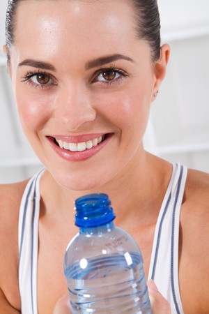 close-up portrait of fitness woman drinking water photo