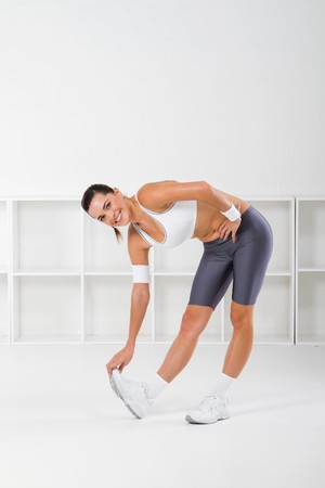 pretty fitness woman stretching indoors Stock Photo - 7639042