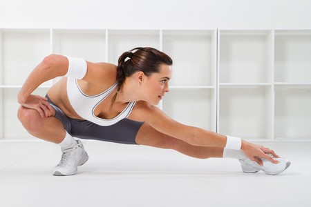 a pretty young fitness woman stretching photo