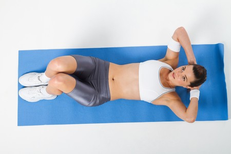 muscle toning: overhead view of woman doing sit-ups Stock Photo