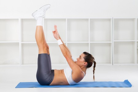 sweats: fit young woman stretching on floor Stock Photo