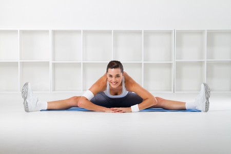 fit, flexible woman stretching in gym photo