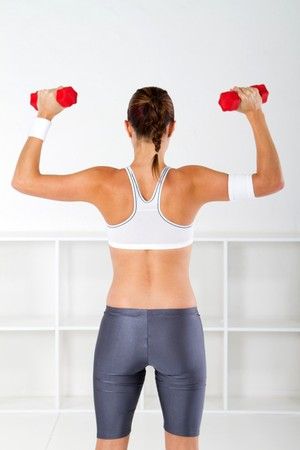 muscle toning: rearview of fitness woman lifting weights