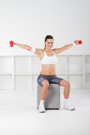 pretty fitness woman lifting weights photo