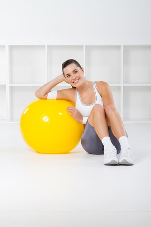 sweats: pretty fit woman leaning against exercise ball