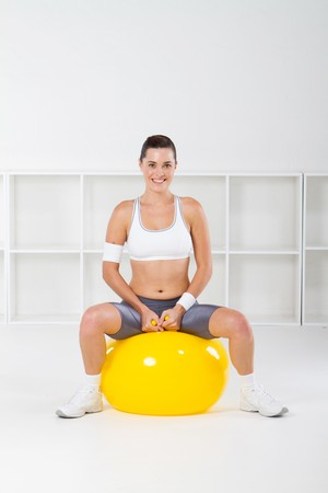 young fitness woman sitting on exercise ball photo
