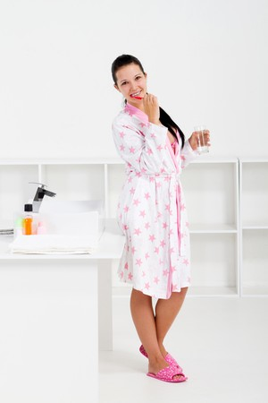 young woman brushing teeth in morning