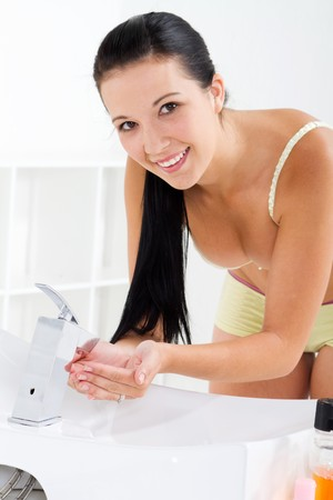 young woman washing hands in sink photo