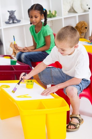 happy young kids painting in classroom photo