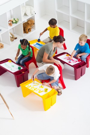 overhead of teacher helping preschool students in class