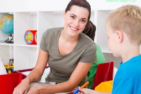 profesor alumno: Pretty profesor con ni�os de jard�n de infancia feliz  Foto de archivo