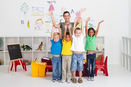 cheerful teacher and preschool kids in classroom photo