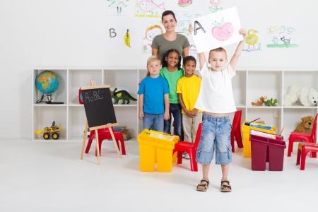 maestra jardinera: feliz ni�o preescolar, mostrando su obra de arte en el aula
