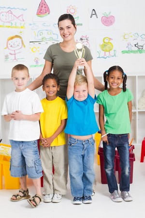 happy preschool boy holding trophy with classmates photo