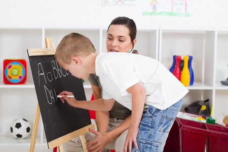 teacher helping young student write on chalkboard photo