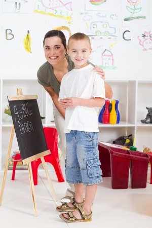 happy young teacher and preschool boy in classroom photo