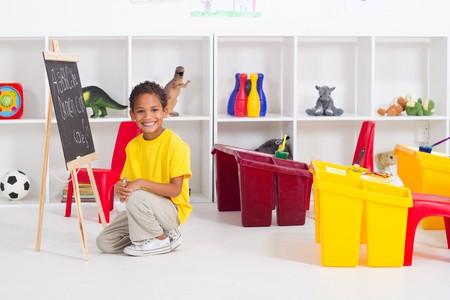 happy indian kindergarten boy in classroom photo