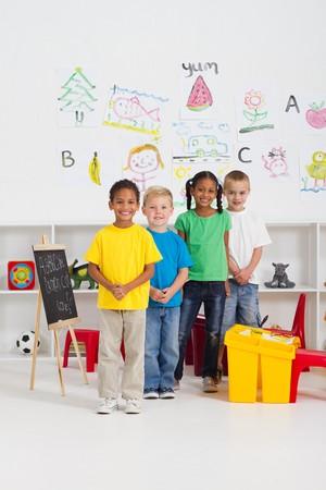diverse students: happy kindergarten classmates in classroom