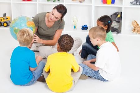 preschool teacher showing children countries on globe Stock Photo - 7795764