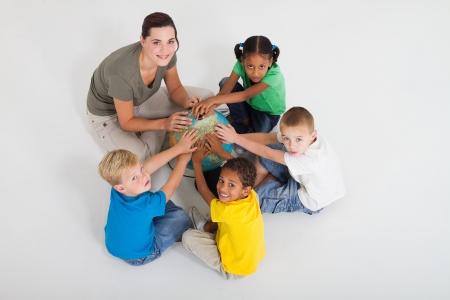multicultureel: leraar en leerlingen handen op wereld bol