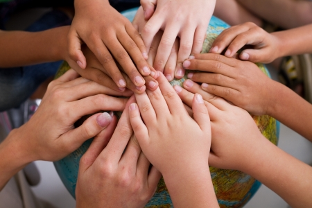 diverse kids hand on globe photo