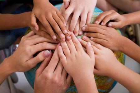 manos juntas: mano de diversos ni�os en globo  Foto de archivo