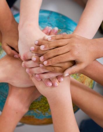 diverse kids hand on globe photo
