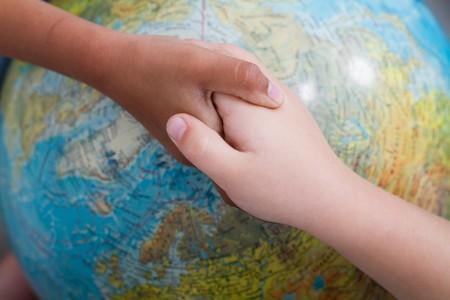kids handshake on globe photo
