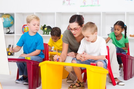 kindergarten teacher: kindergarten teacher helping young students Stock Photo