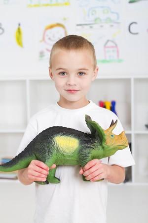 kindergartner: preschool boy playing with dinosaur Stock Photo