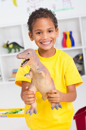 play time: happy indian boy holding plastic dinosaur Stock Photo