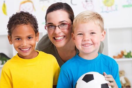 happy preschool teacher with two boys in classroom photo