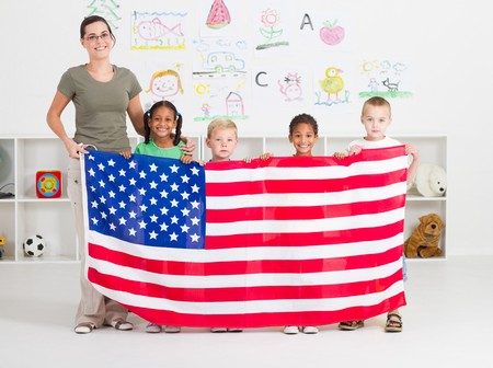 american teacher and preschool students holding flag photo