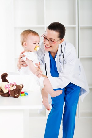 female pediatrician with cute baby girl in clinic photo