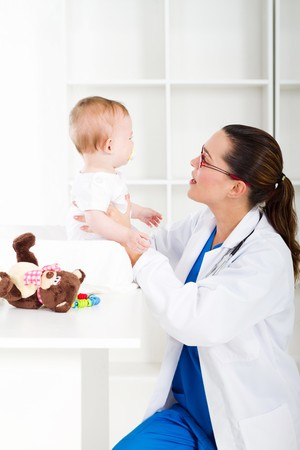 doctor toys: friendly pediatrician checking baby in clinic