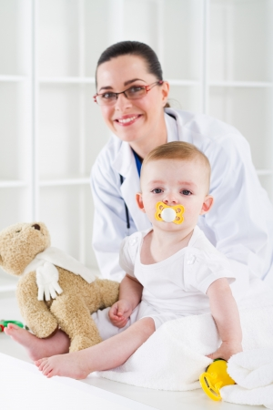 friendly pediatrician and young baby at clinic photo