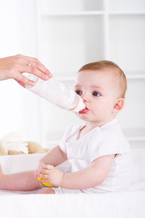 cute baby drinking bottle of milk photo
