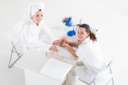 white robe: woman having manicure in beauty salon
