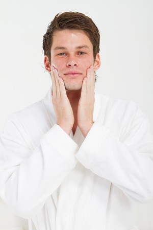 metrosexual: young man applying aftershave in morning Stock Photo