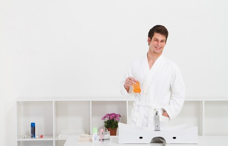 minty: young man using mouthwash in bathroom